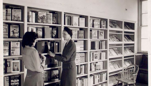 """Librarian with young reader in Browsing Room of the Nathan Strauss Branch for Young People"" The New York Public Library Digital Collections."